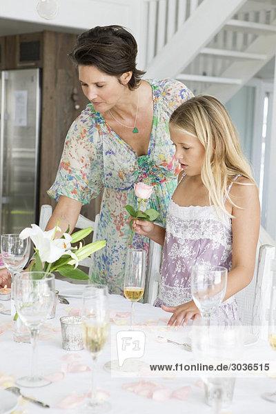 Frau arrangiert einen Tisch für eine Party mit ihrer Tochter