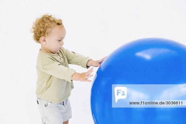Junge spielt mit einem Fitnessball