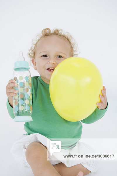 Kleiner Junge mit Ballon und Babyflasche