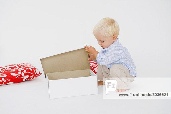 Baby Junge öffnet eine Schachtel