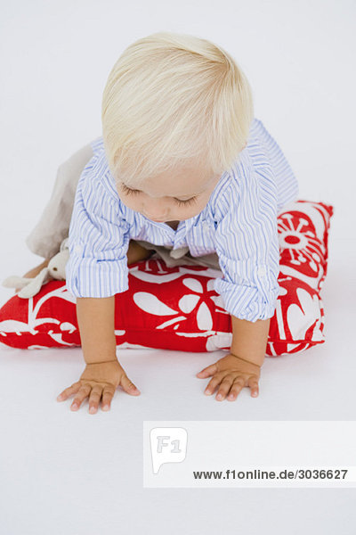 Kleiner Junge krabbelt auf einem Kissen