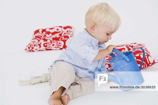 Junge spielt mit der Gießkanne