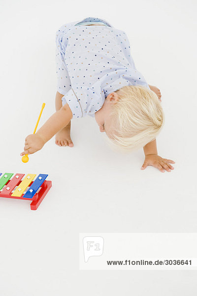 Kleiner Junge spielt mit einem Xylophon