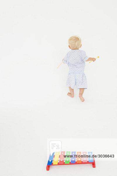 Xylophon mit einem kleinen Jungen  der mit Schlägeln im Hintergrund läuft.