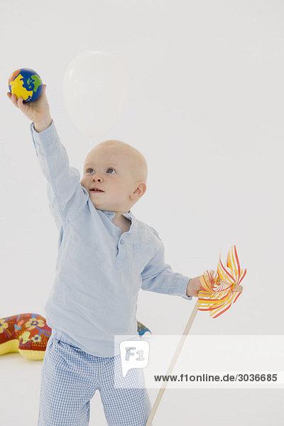 Kleiner Junge hält einen Ball hoch