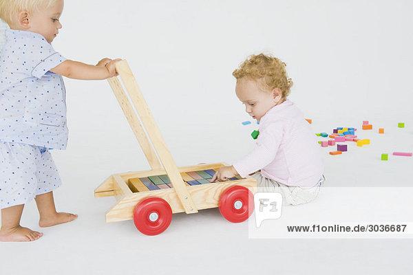 Zwei kleine Jungen  die mit einem Schubkarren spielen.