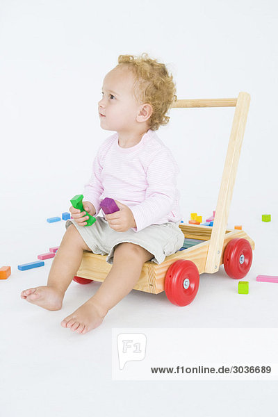 Kleiner Junge sitzt auf einem Schiebewagen