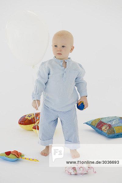 Baby Junge stehend mit Spielzeug