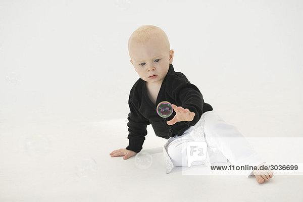 Baby Junge greift nach einer Seifenblase