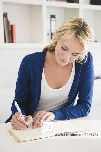 Geschäftsfrau beim Schreiben auf einem Notizblock