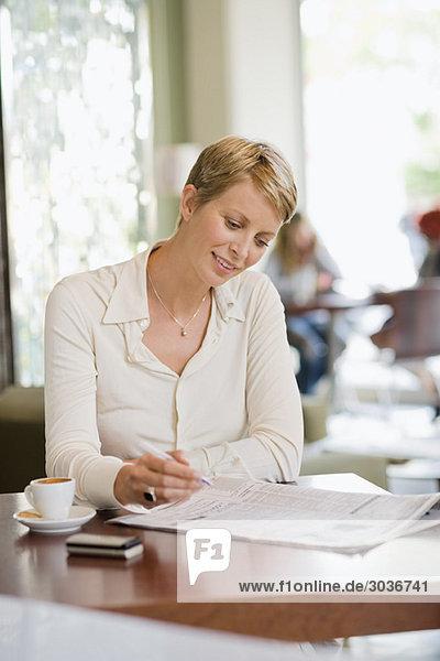 Geschäftsfrau sitzt in einem Restaurant und liest eine Finanzzeitung.