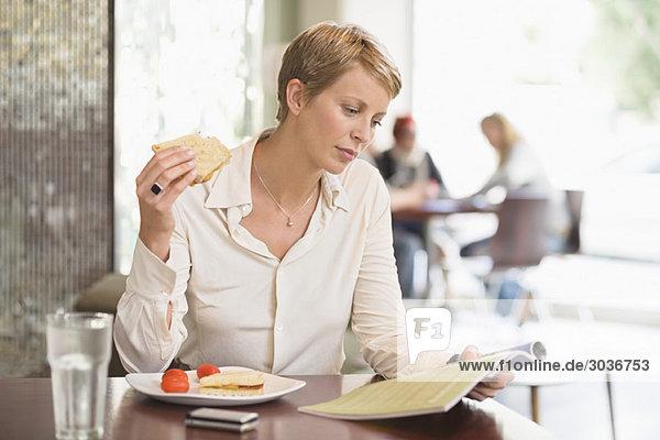 Geschäftsfrau sitzt in einem Restaurant und liest eine Zeitschrift.
