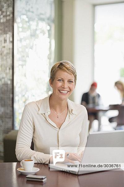 Geschäftsfrau bei der Arbeit am Laptop in einem Restaurant