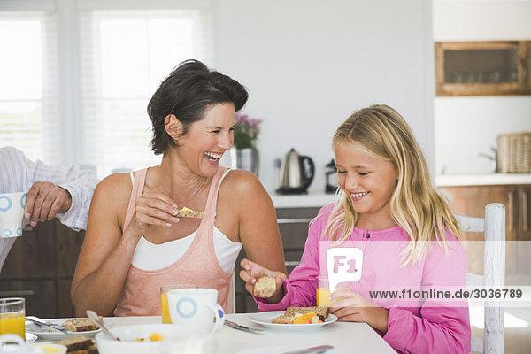 Frau beim Frühstück mit ihrer Tochter am Esstisch