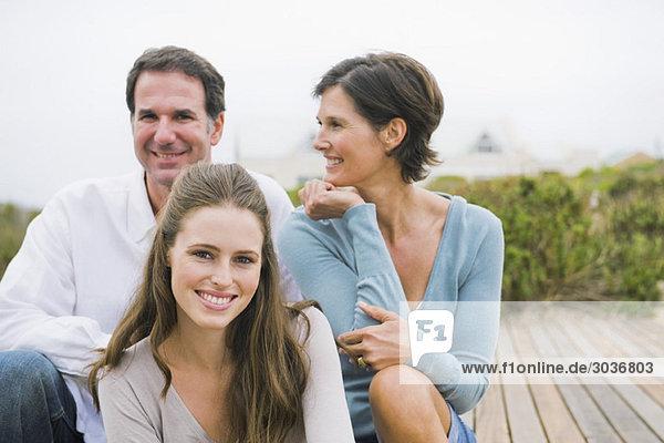 Frau sitzt mit ihren Eltern auf einer Strandpromenade