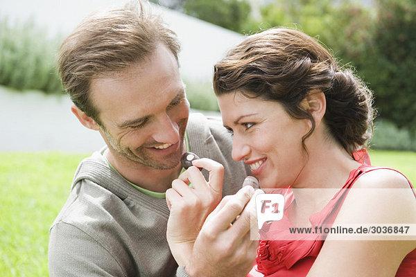 Paare füttern sich gegenseitig mit Schokolade und lächeln