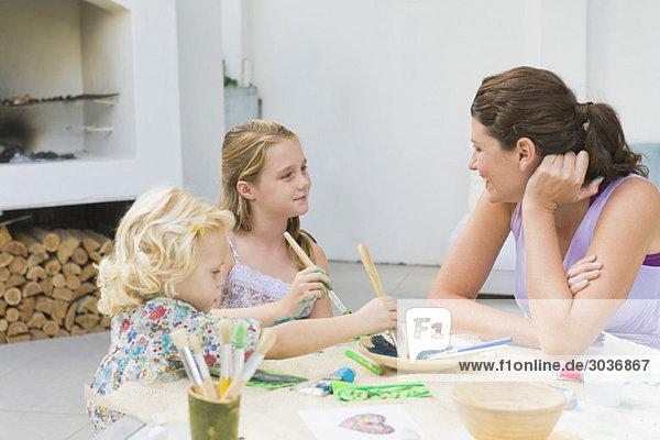 Frau unterrichtet ihre beiden Töchter.