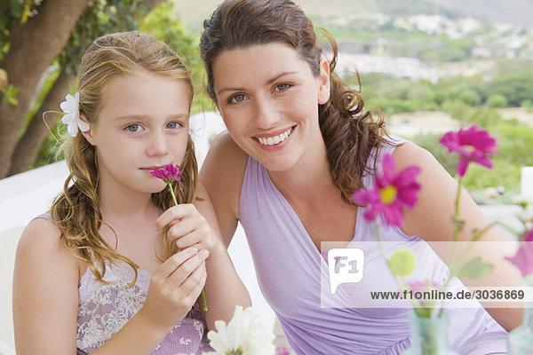 Porträt einer Frau  die mit ihrer Tochter lächelt