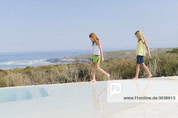 Zwei Mädchen  die auf dem Sims eines unendlichen Pools laufen.