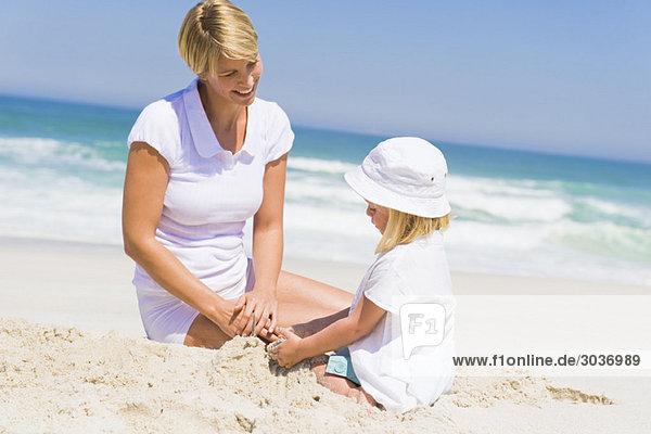 Frau sitzend mit ihrer Tochter am Strand
