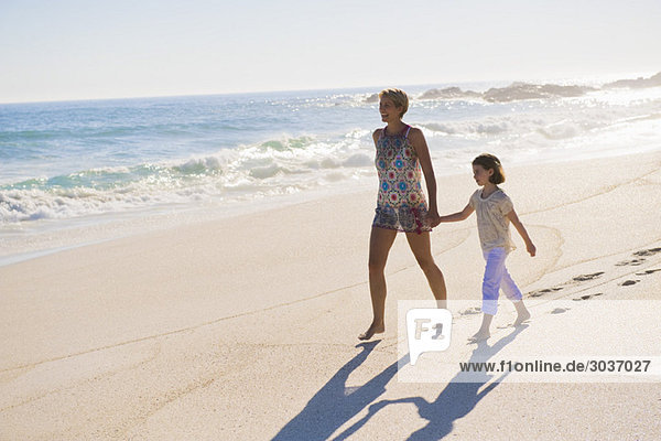 Frau  die mit ihrer Tochter am Strand spazieren geht.