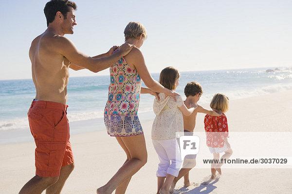 Familienwanderung am Strand in Zugformation