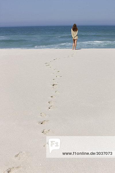 Rückansicht einer am Strand stehenden Frau