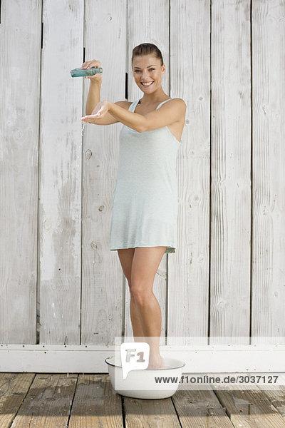 Frau mit einer Shampooflasche im Bad