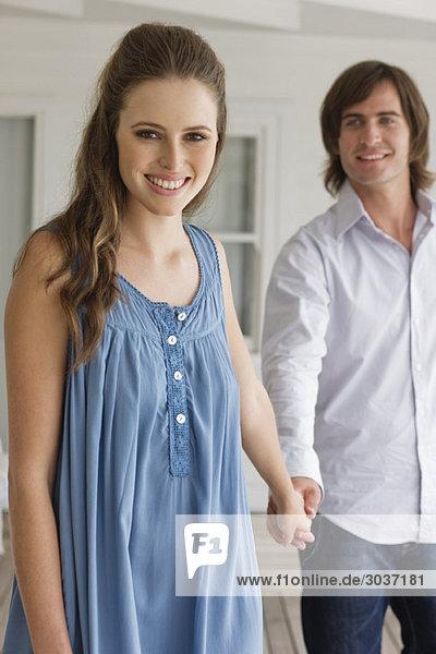 Ein Paar hält sich an den Händen und lächelt.