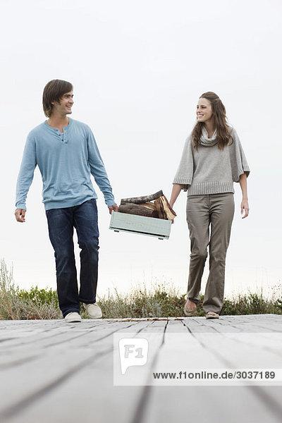 Paar mit Brennholz auf einer Promenade