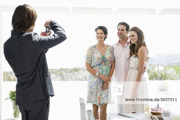 Bräutigam fotografiert die Braut mit ihren Eltern auf einer Hochzeitsfeier.