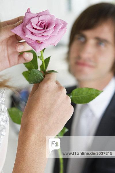 Eine Frau hält eine Blume vor einem Mann.