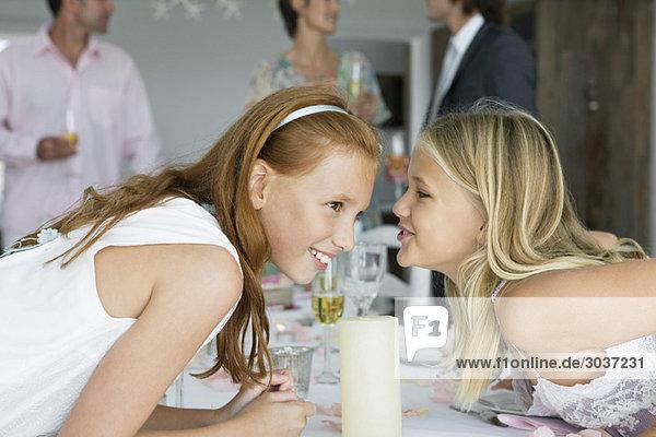 Mädchen flüstert ihrer Schwester über einen Esstisch zu.