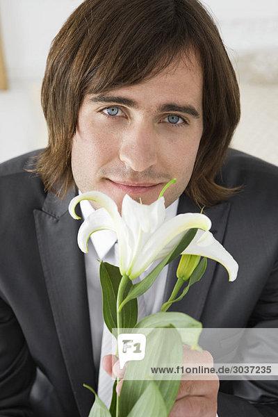 Bräutigam sitzt auf dem Bett und hält eine Lilienblume.
