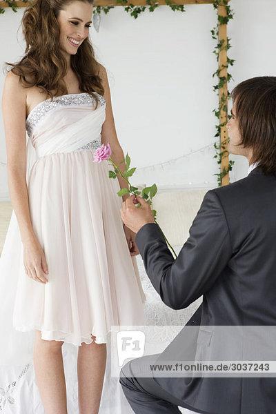 Mann  der einer Frau im Schlafzimmer eine Blume schenkt.