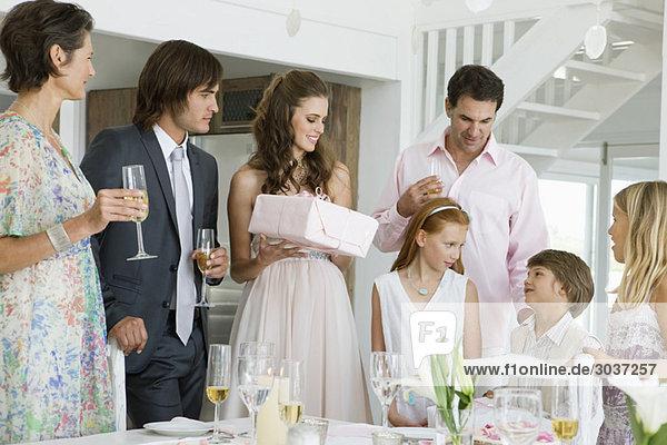 Braut erhält ein Geschenk von einem Gast in einer Party