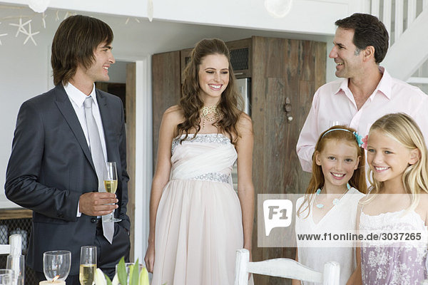 Newlywed couple enjoying with guests in a party