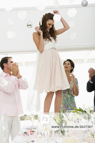 Neuvermähltes Paar mit Gästen bei einer Hochzeitsfeier