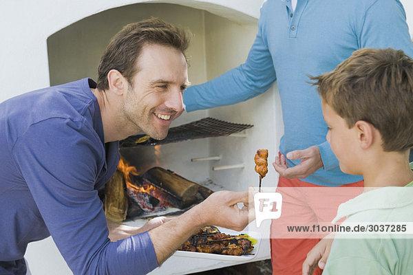 Nahaufnahme eines Mannes  der seinem Sohn gebratenes Kebab gibt.