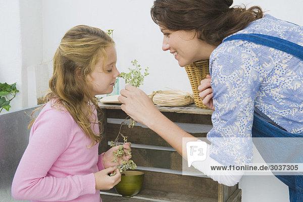 Frau hält die Pflanze mit ihrer Tochter  die sie riecht.