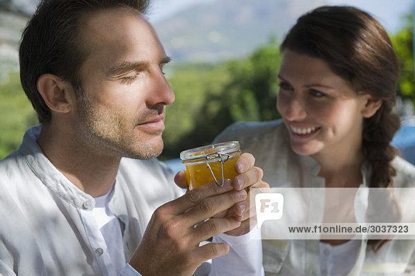 Mann riecht Marmelade mit einer Frau  die neben ihm lächelt.