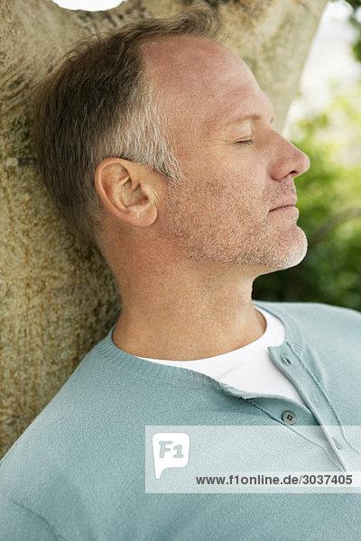 Mann lehnt sich an einen Baum und denkt nach