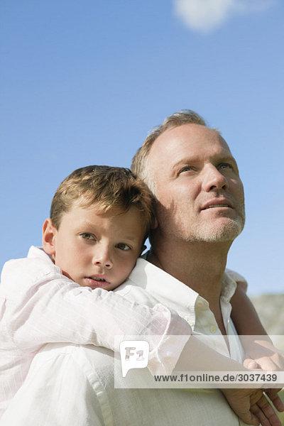 Junge reitet Huckepack auf seinem Vater.