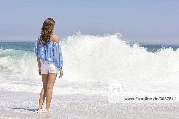 Frau am Strand stehend und mit Blick auf die Aussicht