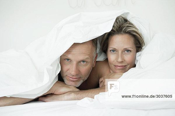 Paar in Bettdecke gewickelt