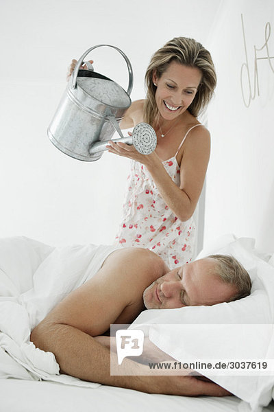 Frau gießt Wasser mit einer Gießkanne auf einen Mann  der auf dem Bett schläft.