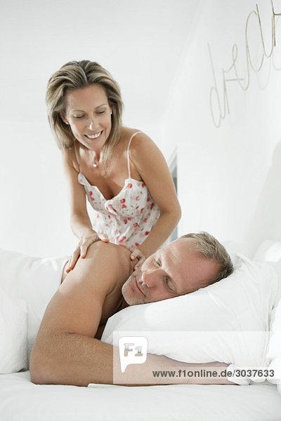 Frau weckt einen Mann  der auf dem Bett schläft.