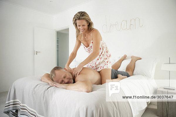 Frau massiert Rücken eines Mannes