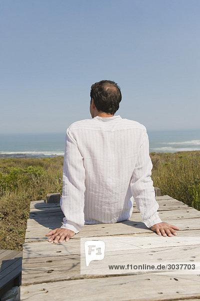 Rückansicht eines Mannes auf einer Strandpromenade