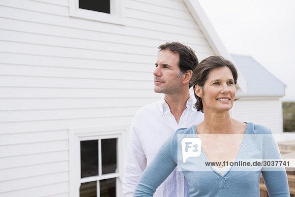 Paar steht zusammen vor einem Haus